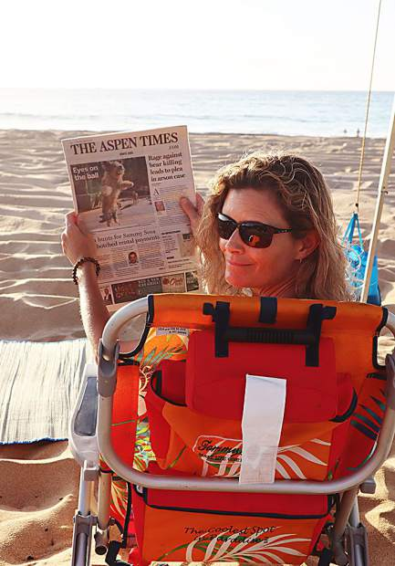 Sarah Manning of Aspen keeps tabs on happenings back home as she relaxes on the longest stretch of beach in the state of Hawaii. Polihale Beach on Kauai is accessed via an unpaved, former cane haul road, spanning 17 miles of white sand and sand dunes, just south of the renowned Na Pali Coast.
