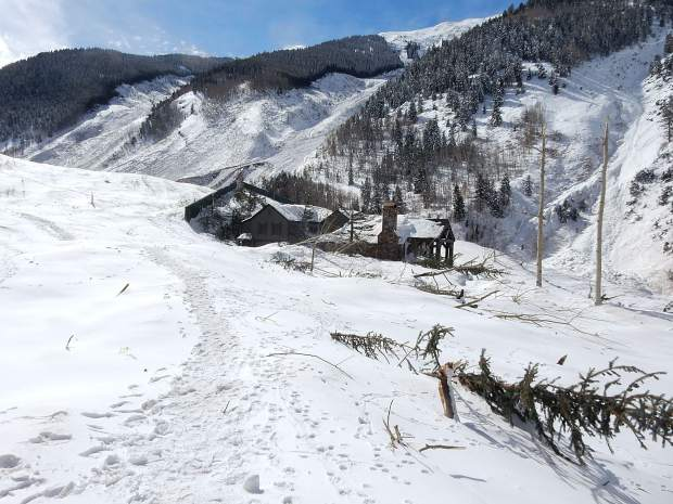 The last house on Conundrum Road was surrounded by snow and debris from an avalanche that came down the K Chute, far left, and Fiver Fingers, middle, on March 8 or 9.
