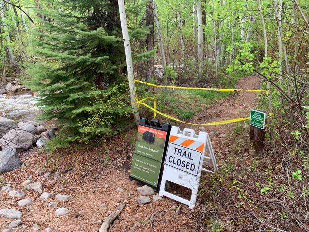 A trail closure sign blocks the lower Hunter Creek Valley trail to hikers Monday afternoon after an unprovoked bear attack was reported earlier in the day. Crews with tracking dogs were dispatched to locate the suspect bear.