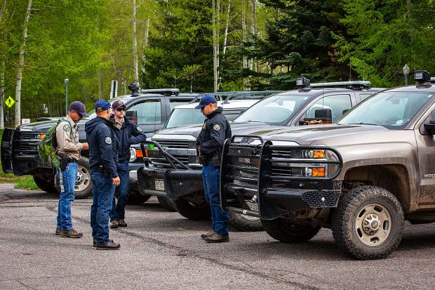Colorado Parks and Wildlife officials wait at the lower Hunter Creek Valley trailhead (near the Hunter Creek apartments) on Monday for dog teams to track down a black bear that reportedly attacked a hiker earlier that day.