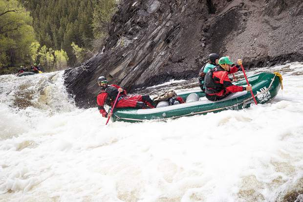Elk Mountain Expeditions guide Tom Wills, left, and owner James Foerster, front right, and Shaffer Klenda after rafting down Slaughterhouse Falls on the Roaring Fork River on May 16.