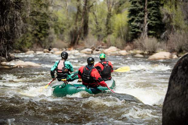 Elk Mountain Expeditions guide Tom Wills guiding on the Slaughterhouse falls section on the Roaring Fork River on May 16 with owner James Foerster, right, and guide Shaffer Klenda.
