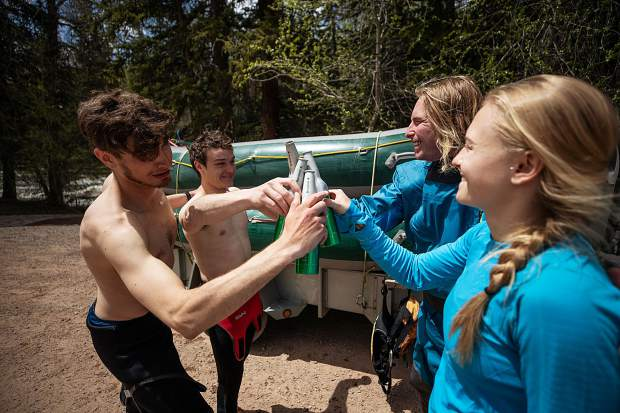 Elk Mountain Expeditions raft guide Curtis Berklund, right, cheers beers with friends at Jaffee Park after going on a trip on May 16.
