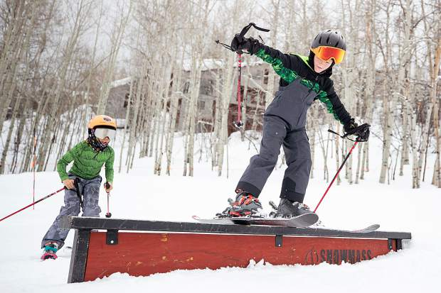 Trey Beard, 8, hits a rail in a Snowmass resort terrain park and is cheered on by Andrew Huck, 9, on March 23, 2019.