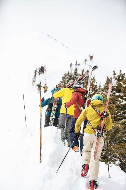 Skiers and snowboarders hike up Highland Bowl April 14, 2019.