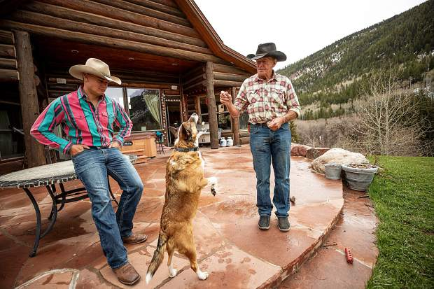 T-Lazy 7 Ranch owner Rick Deane plays with his dog Gracie with his son Jesse.