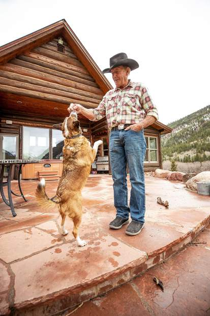 T-Lazy 7 Ranch owner Rick Deane plays with his dog Gracie.