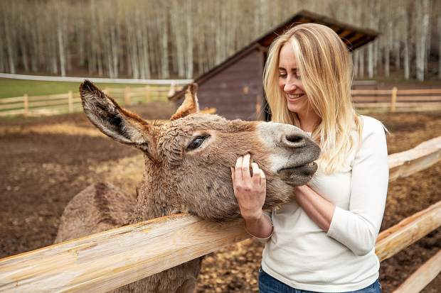 Besha Deane pets one of their donkeys at T-Lazy 7 Ranch.
