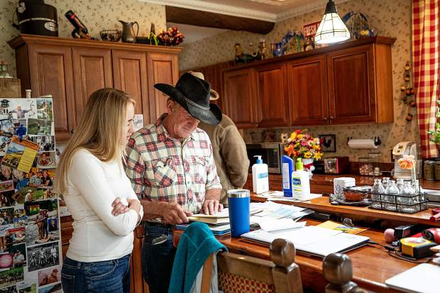 Rick Deane looks at an old book with his daughter Besha in his home at his ranch at T-Lazy 7.