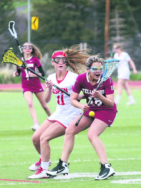 Aspen High School senior Juna Rettig, left, battles for the ball in the girls lacrosse game against Telluride on Saturday, May 4, 2019, on the AHS turf. (Photo by Austin Colbert/The Aspen Times).