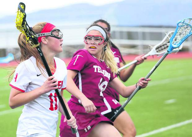 Aspen High School senior Juna Rettig, left, brings the ball upfield in the girls lacrosse game against Telluride on Saturday, May 4, 2019, on the AHS turf. (Photo by Austin Colbert/The Aspen Times).