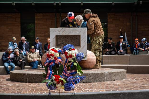 Nancy Bosshard, an Air Force pilot in Vietnam who played an instrumental role in the creation of the original Veterans Memorial Park, gets assistance Monday to light a candle Monday to commemorate the Memorial Day celebration in Aspen.