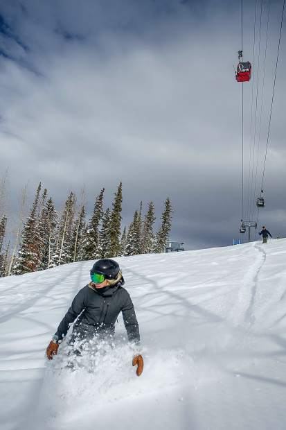 Aimee Acklen and Trent Jones ride and ski through powder under the Silver Queen Gondola on Aspen Mountain on Jan. 17, 2019.