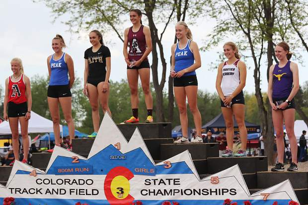 Aspen High School sophomore Kendall Clark, far left in sixth, and Basalt senior Megan Maley, far right in seventh, stand on the podium after placing in the 3A girls 800-meter run at the state track and field championships on Friday, May 17, 2019, in Lakewood.