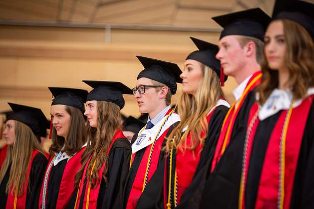 Seniors stand to receive their dimplomas at Aspen High School's graduation Saturday at the Benedict Music Tent.
