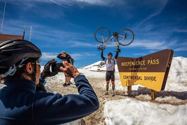 Rick Warren of Ft. Huachuca, Arizona, poses for a photo next to the Independence Pass sign after climbing up the Twin Lakes side on day three of Ride the Rockies Tuesday.