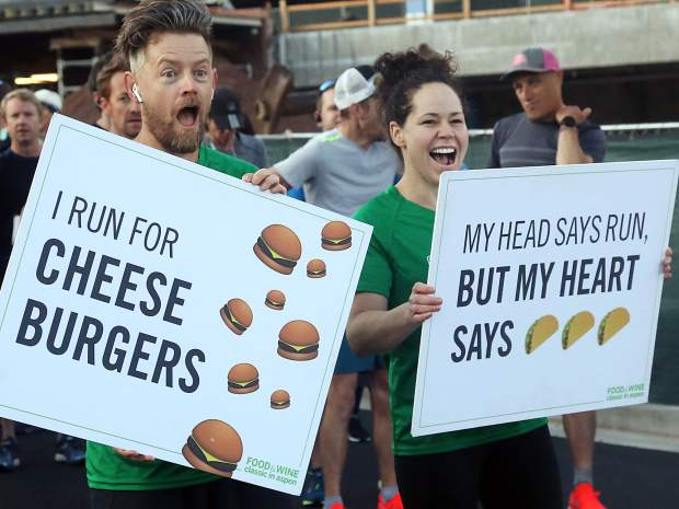 Chefs Richard Blais and Stephanie Izard cheer on the crowd Friday morning at the annual Food & Wine 5k charity run at Rio Grande Park.