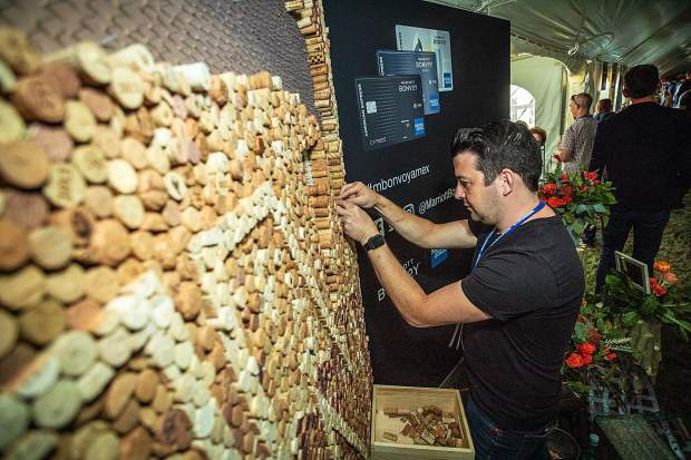 Artist Scott Gundersen works on his cork mural installation in the Food & Wine Classic tasting tent Saturday.