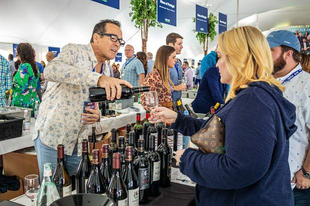 Wine expert Alex Guarachi pours a glass for guests in the Grand Tasting Tent Friday.