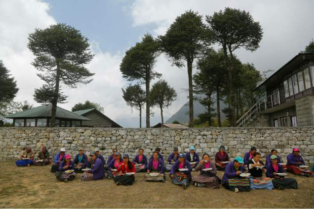 In this May 27, 2019 photo, Nepalese Sherpa community women eat their lunch during a function to announce Mount Everest cleanup campaign in Namche Bajar, Solukhumbu district, Nepal. The record number of climbers on Mount Everest this season has left a cleanup crew grappling with how to clear away everything from abandoned tents to human waste that threatens drinking water. (AP Photo/Niranjan Shrestha)
