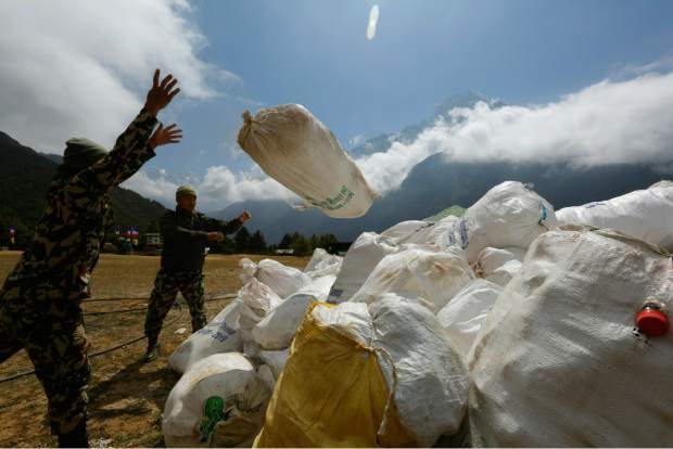 In this May 27, 2019 photo, Nepalese army men pile up the garbage collected from Mount Everest in Namche Bajar, Solukhumbu district, Nepal. The record number of climbers on Mount Everest this season has left a cleanup crew grappling with how to clear away everything from abandoned tents to human waste that threatens drinking water. (AP Photo/Niranjan Shrestha)