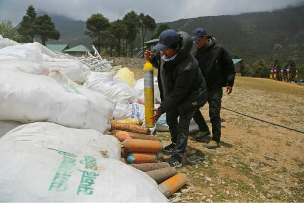 In this May 27, 2019 photo, members of garbage retrieval expedition pile up empty oxygen cylinders collected from Mount Everest in Namche Bajar, Solukhumbu district, Nepal. The record number of climbers on Mount Everest this season has left a cleanup crew grappling with how to clear away everything from abandoned tents to human waste that threatens drinking water. (AP Photo/Niranjan Shrestha)
