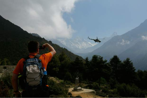 In this May 27, 2019 photo, a tourist takes a photograph of the Mount Everest at Namche Bajar, Solukhumbu district, Nepal. The record number of climbers on Mount Everest this season has left a cleanup crew grappling with how to clear away everything from abandoned tents to human waste that threatens drinking water. (AP Photo/Niranjan Shrestha)