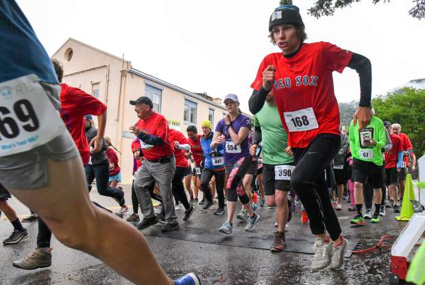 Runners take off at the starting line of the 5K Strawberry Shortcut near 9th and Grand on a wet and cold Sunday morning in downtown Glenwood.