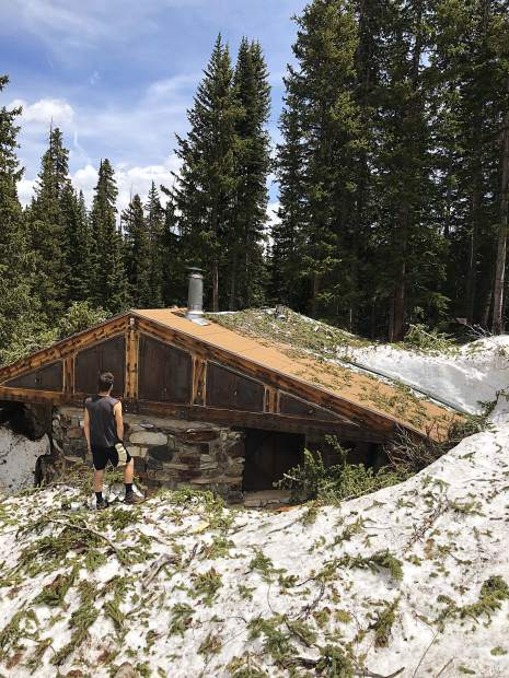 A hiker stands in front of the Mace Hut on Sunday.