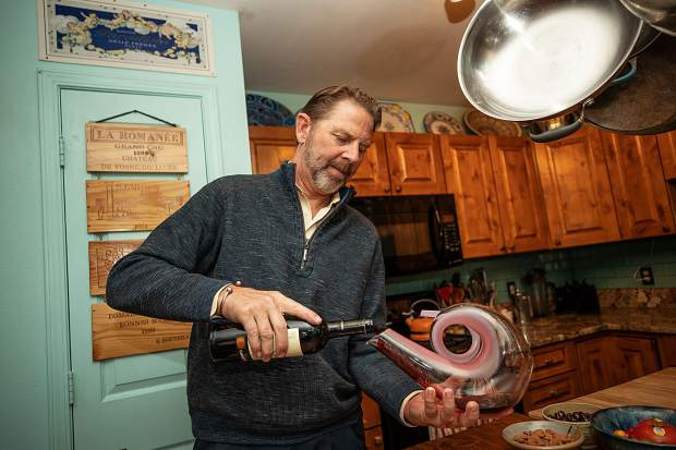 Master Sommelier Jay Fletcher pours wine in a canter at his home on Juan Street in Aspen.
