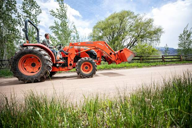 Rock Bottom Ranch Agriculture Manager Alyssa Barsanti undertakes chores using the ranch's tractor on May 23.