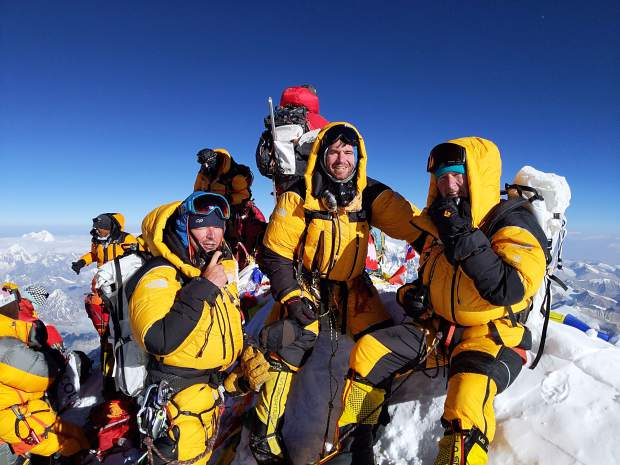 Tony Caine (right) celebrates at the summit of Mount Everest with members of his climbing team. They made the summit on May 23.