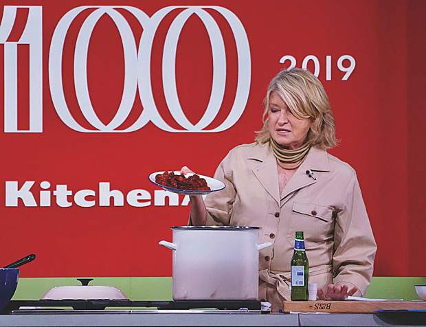 Martha Stewart slidas a plate of chorizo into a clambake during a cooking demo at the St. Regis Aspen.
