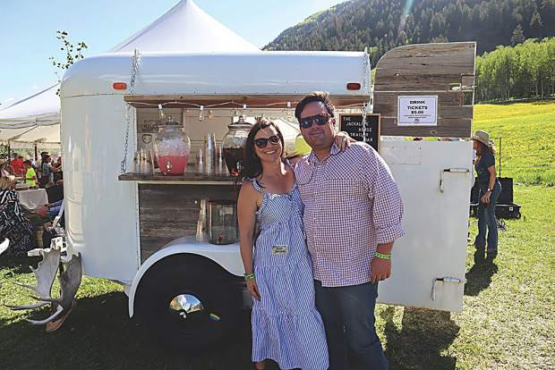 Jordan and Zach Matthews with Go West Event Rentals beside their vintage horse trailer bar.
