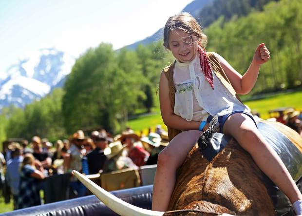 A young girl rides a mechanical bull at the T-Lazy-7 Ranch 80th anniversary hoedown on Saturday, June 8, 2019. (Photo by Austin Colbert/The Aspen Times)