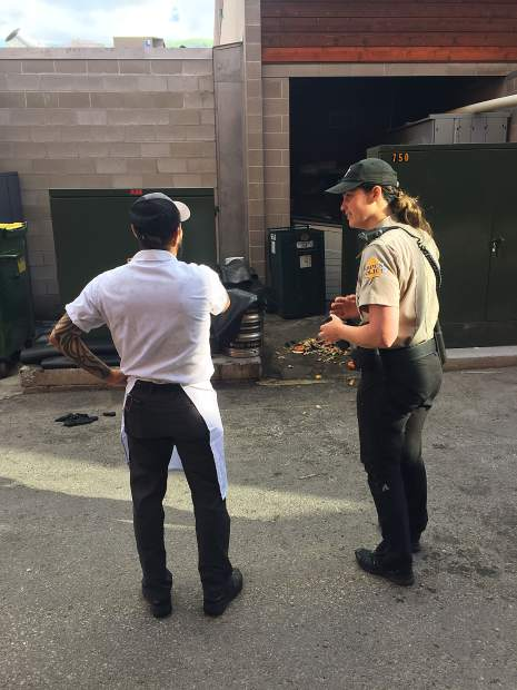 Aspen Community Response Officer Alyse Katynski explains to an employee of Clark's Oyster Bar why it's important to keep human food locked up so it doesn't attract bears. In front of them is bear scat and a knocked over compost container.
