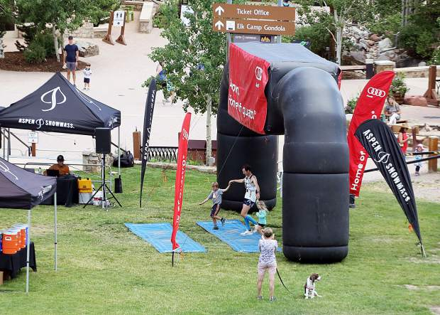Gunnison's Joshua Eberly, with help from his children, crosses the finish line to win the Audi Power of Four trail run on Saturday, July 13, 2019. (Photo by Austin Colbert/The Aspen Times)