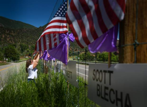 Canyon Creek resident Lynette Cerise hangs flags and purple ribbons along with the names of the 14 wildland fire fighters who lost their lives 25 years ago in the South Canyon fire.
