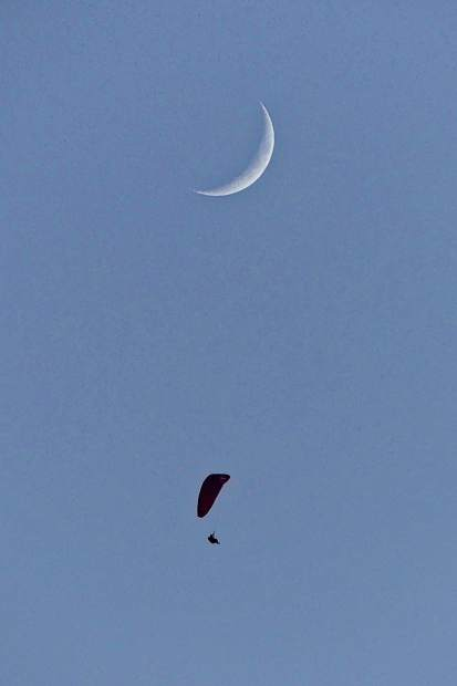 Reader Kathryn Rabinow captured a photograph of this paraglider under a waxing crescent moon on Friday evening.