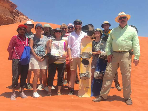 From left, Roaring Fork Valley residents Nalini Roa, Frank Taverna, Laura Kornasiewicz, Sharon Taverna, Nancy Beckwith, Anna Maria Whalen and Steve Beckwith show off their Aspen Times with some sand boarders in Wadi Rum, Jordan, on July 1.