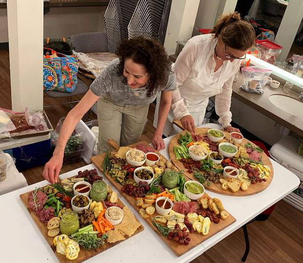 Elizabeth Plotke and Nancy Paley prepare Campo Catering's signature antipasti boards at a recent party.
