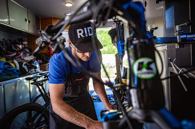 Mark Welgos tunes a bike in his mobile bike repair trailer.