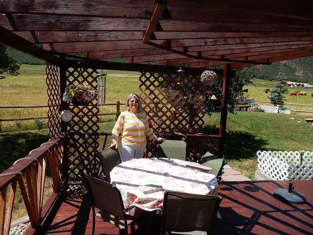 Marti Barbour stands on the arbor on the rear deck of her house in Emma. She and her family worked hard to make their house a home.