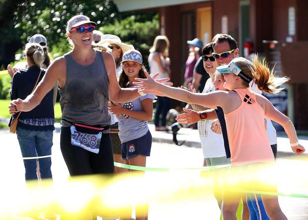 Aspen's Shelley Roy gets a high five as she approaches the finish of the Aspen Valley Half Marathon on Saturday, July 13, 2019. (Photo by Austin Colbert/The Aspen Times)