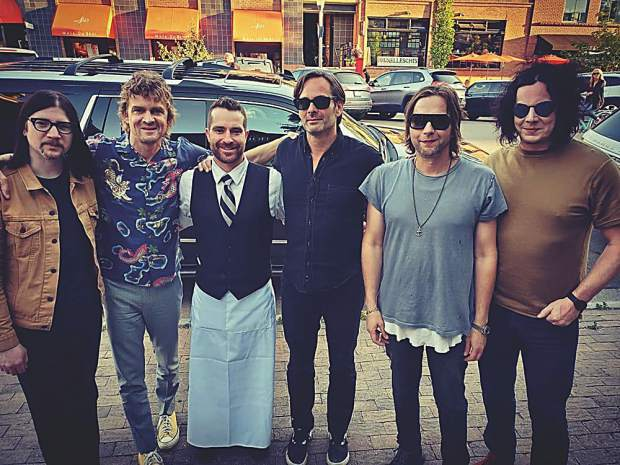 Alex Costa in his Steakhouse 316 uniform alongside the Raconteurs in their rock star attire. Courtesy photo.