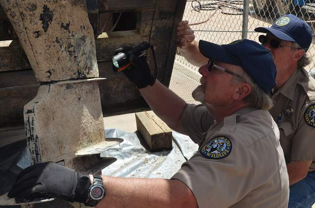 An inspector with Colorado Parks and Wildlife goes over a boat motor looking for invasive mussels at Navajo State Park in June 2018.