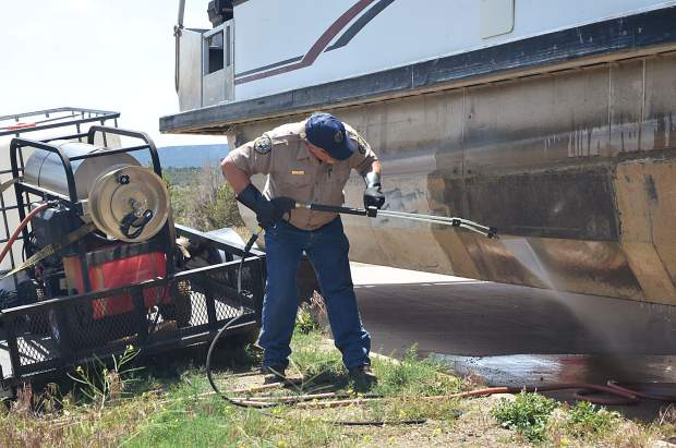 An employee of Colorado Parks and Wildlife decontaminates a boat at Navajo State Park in southwestern Colorado in June 2018. An inspection showed it was carrying mussels.