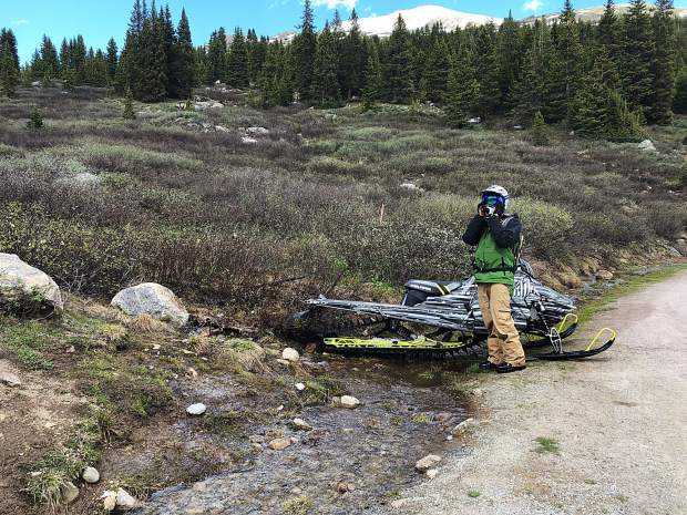 One of two snowmobilers reaches the Upper Lost Man Trailhead parking area on July 3. He and a companion traveled in closed areas and damaged snow-free ground when they exited.
