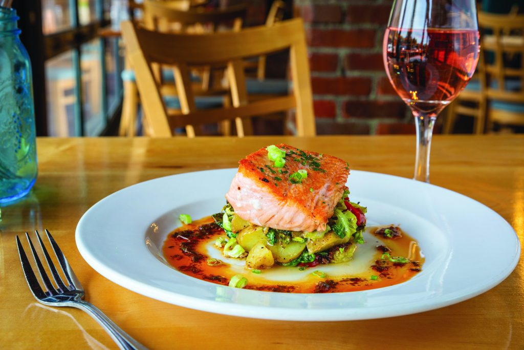 Pan-seared salmon, fingerling potatoes, brussel sprouts, charred tomato and chipotle vin.