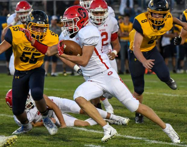 Glenwood Springs Demon Gavin Olson charges through the defending Rifle Bears during last year's rivalry game at Rifle High School.